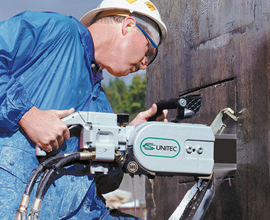Hydraulic concrete chain saw cutting square opening in concrete