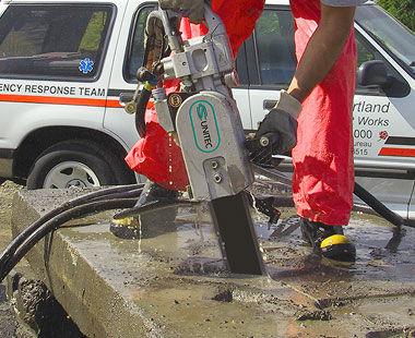 Hydraulic chain saw cutting slab of concrete