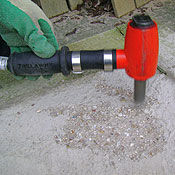 Hand-held low-vibration concrete scabbler