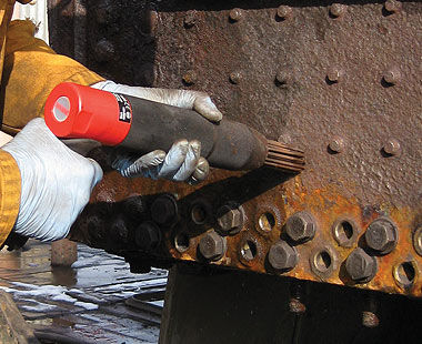 Needle scaler removing rust around bolts on ship deck